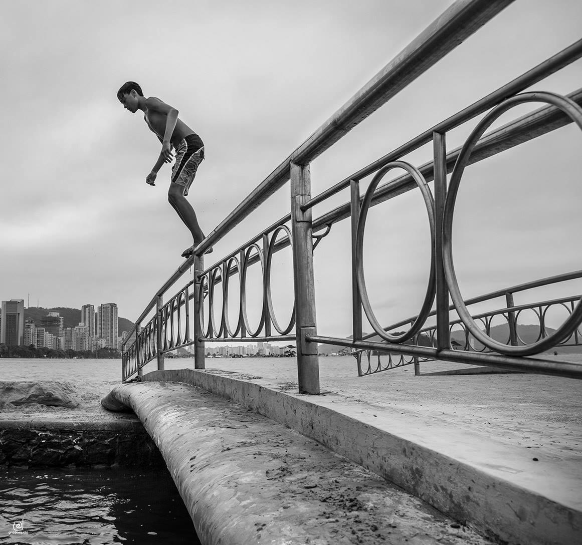 menino mergulhando de uma ponte